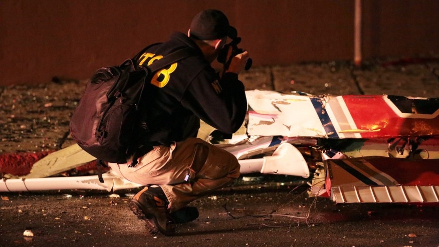 Dec. 29, 2015: A National Transportation Safety Board investigator takes photos at the scene of an aircraft crash in Anchorage, Ak. A small plane clipped a downtown Anchorage office building and then slammed into a nearby commercial building early Tuesday, igniting a fire and killing the pilot, authorities said. (Loren Holmes/Alaska Dispatch News via AP)