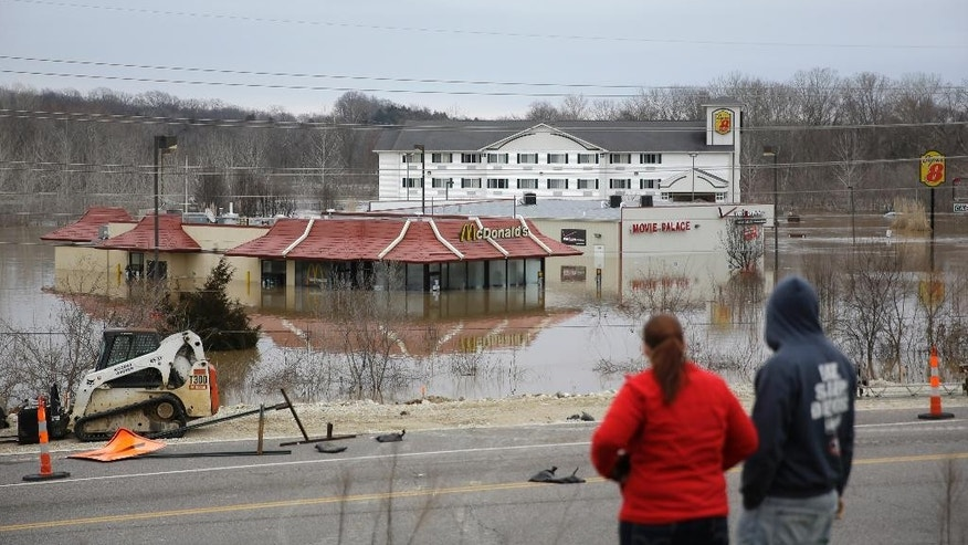 People stand on a hill to get a better look at floodwater from the Bourbeuse River  Tuesday, Dec. 29, 2015, in Union, Mo. Flooding across Missouri has forced the closure of hundreds of roads and threatened homes. (AP Photo/Jeff Roberson)