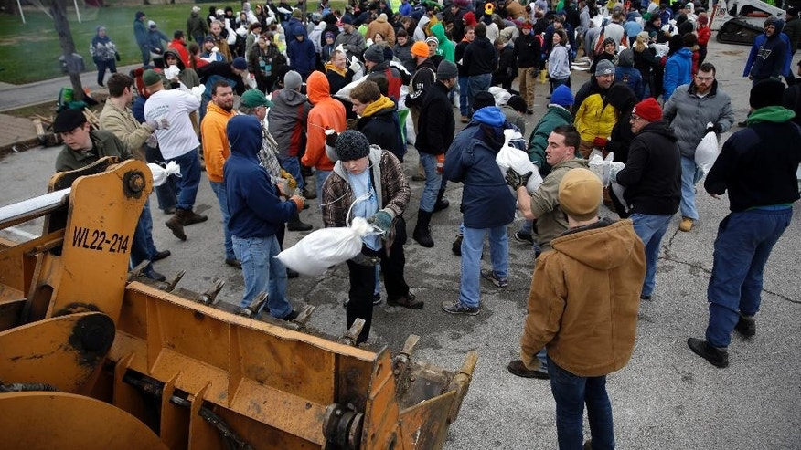 Volunteers form a human chain as they help load sandbags Tuesday, Dec. 29, 2015, in St. Louis. Flooding across Missouri has forced the closure of hundreds of roads and threatened homes. (AP Photo/Jeff Roberson)