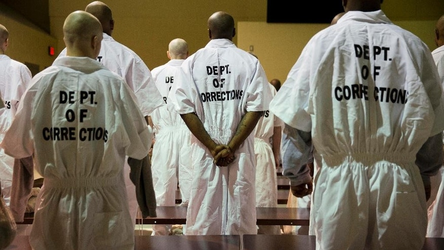 Prisoners stand while being processed for intake at the Georgia Diagnostic and Classification Prison, Tuesday, Dec. 1, 2015, in Jackson, Ga. They arrive by the busload each Tuesday and Thursday, dozens of new inmates entering Georgia's prison system. Most stay only a week or two. But for those sentenced to die, this is their last stop. (AP Photo/David Goldman)