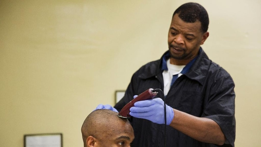 Frederick Harris, right, cuts the hair of Josh Harris, no relation, as he is processed for intake at the Georgia Diagnostic and Classification Prison, Tuesday, Dec. 1, 2015, in Jackson, Ga. When inmates arrive, their possessions are inventoried. Then they shower and don white jumpsuits. They sit in barber chairs while permanent inmates give them close haircuts, then pose for an ID photo. (AP Photo/David Goldman)