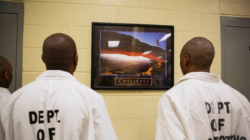 A motivational poster hangs on the wall as prisoners stand at attention while being processed for intake at the Georgia Diagnostic and Classification Prison, Tuesday, Dec. 1, 2015, in Jackson, Ga. The prison, the state's biggest, houses about 2,100 male inmates on a wooded, 900-acre campus about 50 miles south of Atlanta. A warden and three deputy wardens oversee more than 600 employees. (AP Photo/David Goldman)