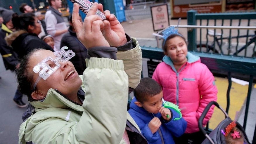 Cynthia Falu, from Dover, Del., celebrates New Year's Eve at noon with her children in Times Square in New York, Thursday, Dec. 31, 2015. Around 1 million people are expected to converge on Times Square for the annual New Year's Eve celebration. This year's festivities will also be attended by nearly 6,000 New York City police officers, including members of a specialized counterterrorism unit. (AP Photo/Seth Wenig)