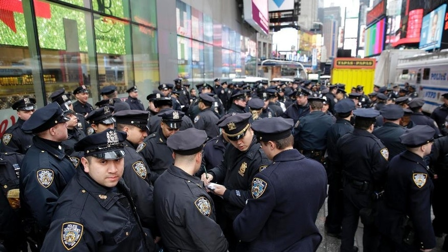 Police officers gather at the southern end of Times Square to receive their assignments for New Year's Eve in New York, Thursday, Dec. 31, 2015. Around 1 million people are expected to converge on Times Square for the annual New Year's Eve celebration. This year's festivities will also be attended by nearly 6,000 New York City police officers, including members of a specialized counterterrorism unit. (AP Photo/Seth Wenig)