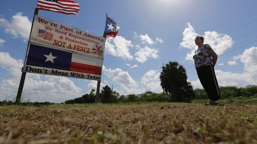 "In this Thursday, Sept. 17, 2015, photo, Pamela Taylor, whose home is on the south side of the border fence, stands near a sign she erected, in Brownsville, Texas. The staggered fence or ""wall,"" costing $6.5 million per mile, runs along  54 miles of Texas' 1,254-mile border with Mexico. She still leaves coolers of water for thirsty migrants, though she wishes more of them would come to the United States legally, the way she emigrated from England.  (AP Photo/Eric Gay)"