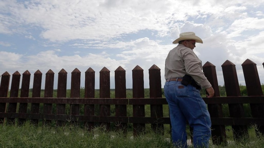 "In this Wednesday, Sept. 16, 2015, photo, farmer Fausto Salinas stands along the border fence, in McAllen, Texas. The staggered fence or ""wall,"" costing $6.5 million per mile, runs along  54 miles of Texas' 1,254-mile border with Mexico. (AP Photo/Eric Gay)"