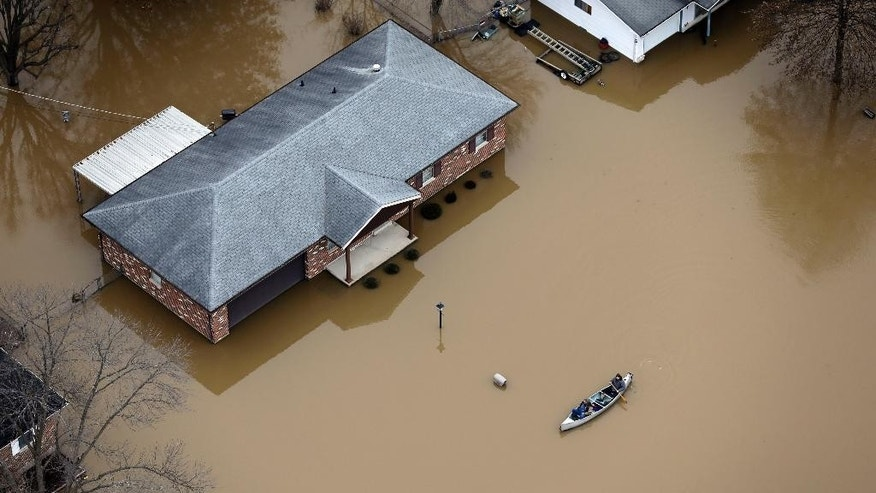 In this aerial photo, people use a canoe to navigate a flooded street, Thursday, Dec. 31, 2015, in Arnold, Mo. Surging Midwestern rivers forced hundreds of evacuations, threatened dozens of levees and brought transportation by car, boat or train to a virtual standstill Thursday in the St. Louis area. (AP Photo/Jeff Roberson)