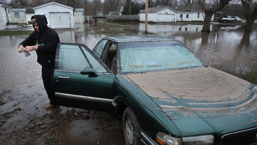 Thomas Barnard removes the registration from fiancee Jessica Klick's 1995 Buick after floodwaters from the South Fork of the Sangamon River receded during a visit to the couple's home in Kincaid, Ill., Thursday, Dec. 31, 2015. The car was almost completely submerged during the flooding. (David Spencer/The State Journal-Register via AP) MANDATORY CREDIT