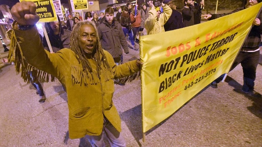 Lee Patterson, left, of Baltimore, joins demonstrators in Baltimore, Tuesday, Dec. 29, 2015, in protest of recent police shootings, including a grand jury's decision not to indict two white Cleveland police officers in the fatal shooting of Tamir Rice, a black 12-year-old boy who was playing with a pellet gun. (AP Photo/Steve Ruark)
