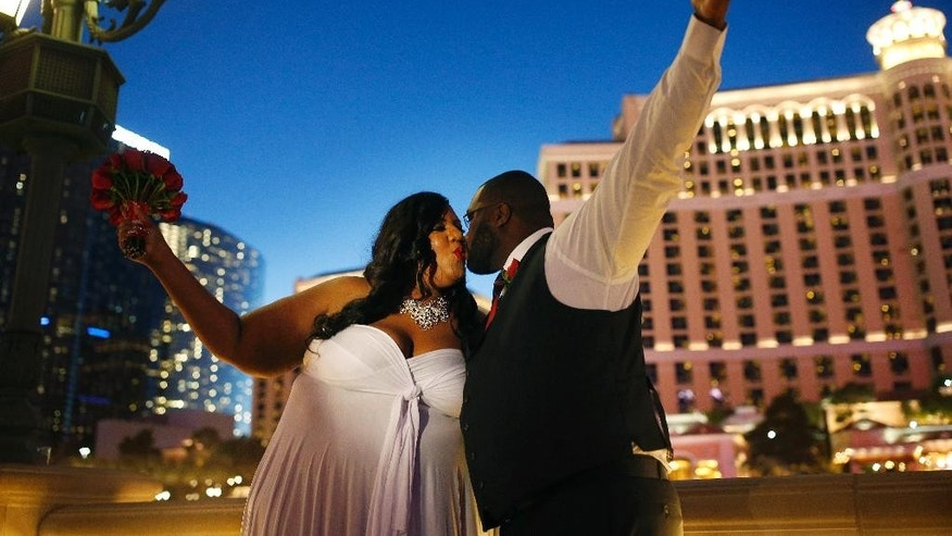 Latoya Gage, left, and her new husband Yaree Gage kiss after getting married along the Las Vegas Strip on New Year's Eve, Thursday, Dec. 31, 2015, in Las Vegas. (AP Photo/John Locher)