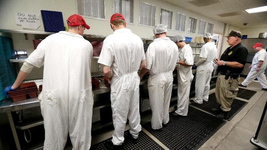 In this photo taken Tuesday, Dec. 8, 2015, corrections officer Kevin Cranston watches inmates working in the kitchen at the Ellsworth Correctional Facility in Ellsworth, Kan. Low wages among Kansas corrections officers are causing many to leave the field, leaving about 9 percent of the positions in the state's prisons unfilled. (AP Photo/Charlie Riedel)