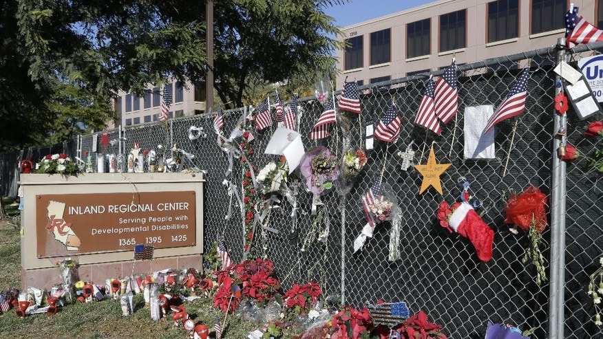 In this Tuesday, Dec. 29, 2015, photo, flowers and American flags honoring the victims of the attack on Dec. 2 are placed outside the Inland Regional Center where the fatal shooting took place in San Bernardino, Calif. At the IRC, Christmas never came. The staff was still gearing up for the holidays on Dec. 2, the day 14 people were massacred on the center's gleaming campus. On Monday, Jan. 4, 2016, they'll return to two of the three buildings not damaged in the rampage. (AP Photo/ Nick Ut)