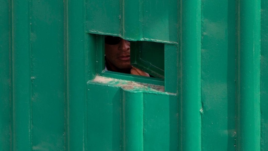 "FILE - In this Dec. 31, 2015 file photo, a guard peers out of a hole in the entrance gate to the Agujas immigration detention center, where U.S. fugitive Ethan Couch is being detained in Mexico City. The Mexican lawyer for a Texas teenager known for using an ""affluenza"" defense in a fatal drunken-driving accident said Monday, Jan. 4, 2016 that his appeal against deportation could delay his client's return to the United States for weeks, perhaps months - or just a single day. (AP Photo/Rebecca Blackwell, File)"