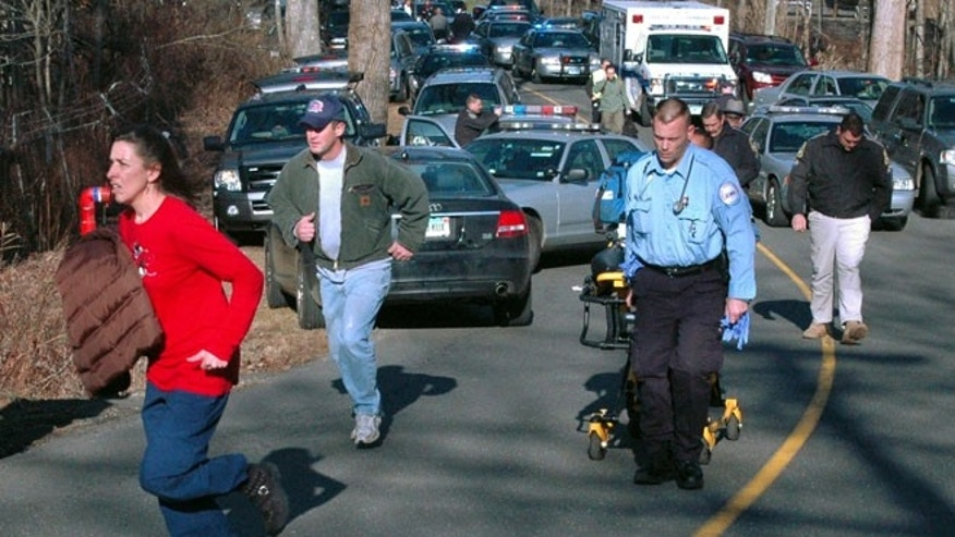 Dec. 14, 2012: In this file photo provided by the Newtown Bee, paramedics and others rush toward Sandy Hook Elementary School in Newtown, Conn., shortly after Adam Lanza opened fire, killing 26 people, including 20 children.
