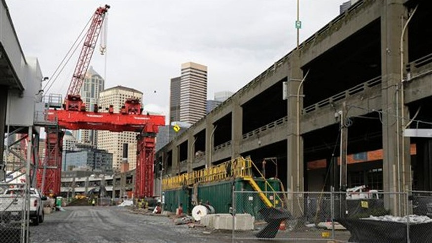 "A crane is shown Friday, Dec. 18, 2015, at the site in Seattle, where an access pit had been dug to repair ""Bertha,"" the massive tunnel boring machine digging a replacement for the Alaskan Way Viaduct elevated roadway, after it hit an underground pipe more than two years ago. Officials have said that the machine could resume tunneling as early as next week.  (AP Photo/Ted S. Warren)"
