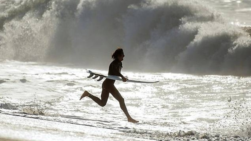 A surfer runs into the ocean at Seal Beach, Calif. on Thursday.