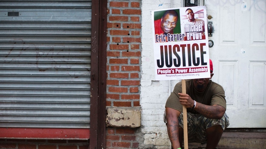 ILE- In this Aug. 23, 2014 file photo, a demonstrator holds a sign bearing the likeness of Eric Garner and Michael Brown before a march to protest the death of Garner in the Staten Island borough of New York.