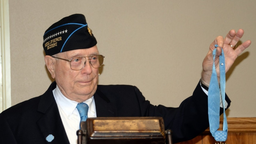 "Hershel ""Woody"" Williams holding his Medal of Honor in 2014."