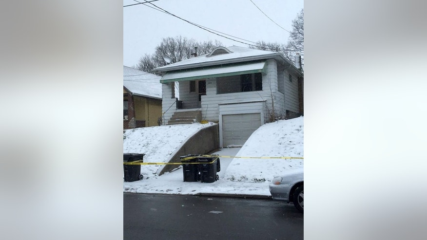Jan. 12, 2016: Police tape cordons off a home in Cincinnati where police say a father, who believed he was confronting an intruder in his home, fatally shot his 14-year-old son. (Patrick Brennan/The Cincinnati Enquirer via AP)