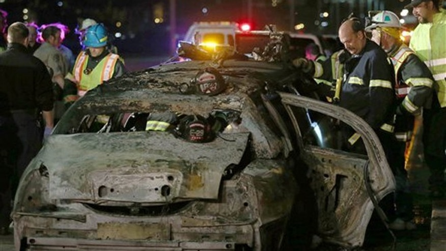 In this May 4, 2013 file photo, San Mateo County firefighters and California Highway Patrol personnel investigate the scene of a limousine fire that killed five passengers on the westbound side of the San Mateo-Hayward Bridge in Foster City, Calif.