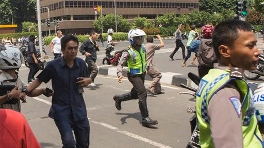 "People, including unarmed police officers, flee from the scene after a gun battle broke out following an explosion in Jakarta, Indonesia Thursday, Jan. 14, 2016. Attackers set off  bombs and exchanged gunfire outside a Starbucks cafe in Indonesia's capital in a brazen assault Thursday that police said ""imitated"" the recent Paris attacks. (AP Photo)"