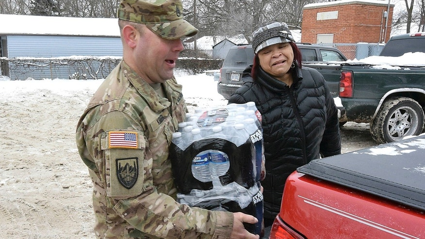 Jan. 13, 2016: Michigan National Guard Sgt. Steve Kiger, left, of Harrison, Mich., carries cases of water for a Flint resident. (Dale G. Young/Detroit News via AP)