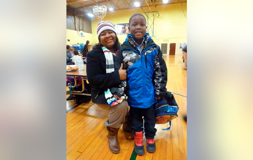 In a photo from Jan. 2, 2016, Sherri Miller and her son, Jameer, 7, a first-grader, are seen at Freeman Elementary School in Flint, Mich., where Jameer was getting his finger-prick blood sample tested for lead. The school has been on bottled water since October when the Michigan Department of Environmental Quality urged parents to get their children tested after water showed lead levels exceeded federal standards by more than six times. (AP Photo/Roger Schneider)