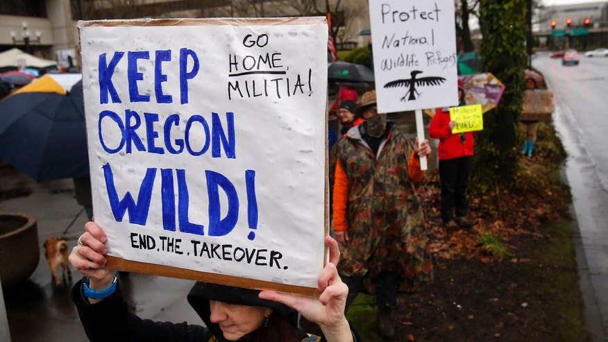 Jan. 19, 2016: Renee Irvin holds a sign during a rally against the occupation of the Malheur National Wildlife Refuge by Ammon Bundy and his armed followers, while joining the rally at the Federal Building in Eugene, Ore. (Andy Nelson/The Register-Guard via AP)