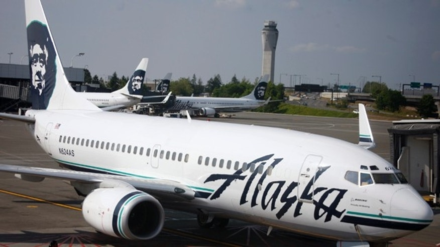In this June 11, 2009 file photo, an Alaska Airlines airliner is pushed away from a gate at SeaTac Airport in SeaTac, Wash.