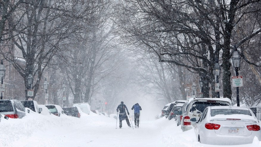 Two people cross-country ski up Marlborough Street during a blizzard in Boston, Massachusetts Jan. 27, 2015.