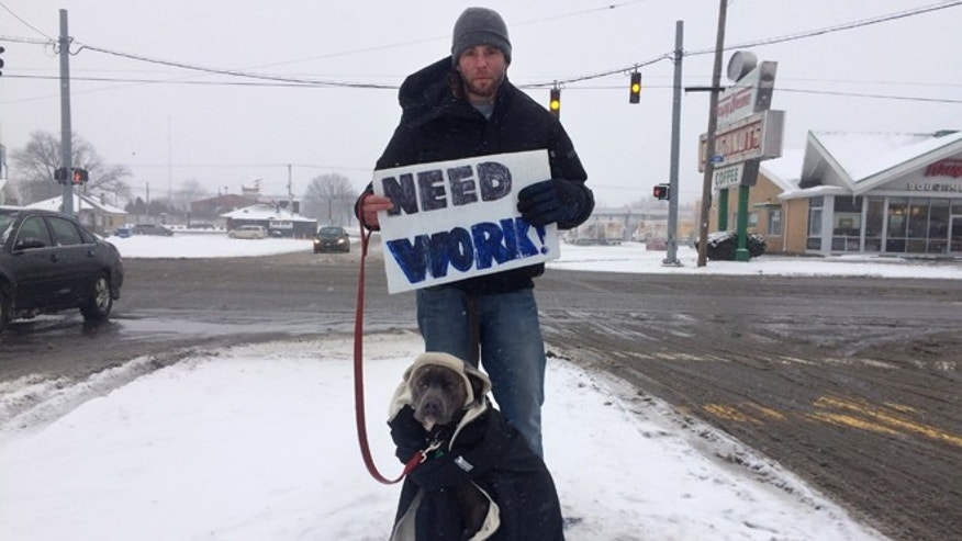 Jan. 22, 2016: Shawn Harmon, a homeless man, holds a sign asking for work outside a supermarket in Louisville, Ky., with his dog, Tucker. (AP Photo/Claire Galofaro)