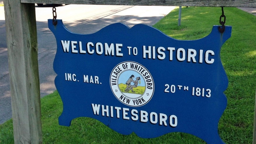 n this photo taken July 16, 2015, a welcome sign on the village green, Whitesboro, N.Y., displays the village seal.
