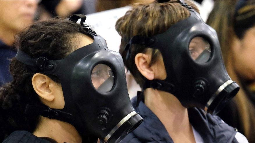 FILE - In this Jan. 16, 2016 file photo, protestors wearing gas masks attend a hearing over a gas leak at the southern California Gas Company's Aliso Canyon Storage Facility near the Porter Ranch section of Los Angeles.