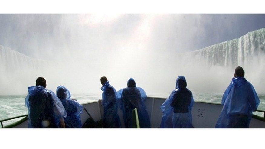 A group of tourists brave opening day on the bow of the Maid of the Mist at the base of the falls.