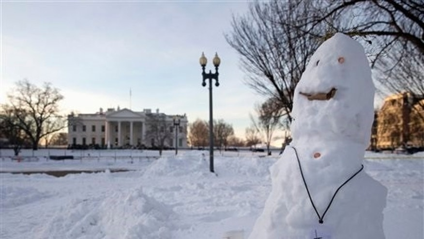 A snowman with a pretend NSA (National Security Agency) badge and a coffee cup stands in Lafayette Square Park, across from the White House in Washington, Monday, Jan. 25, 2016. East Coast residents who made the most of a paralyzing weekend blizzard face fresh challenges as the workweek begins: slippery roads, spotty transit service mounds of snow, and closed schools and government offices.(AP Photo/Carolyn Kaster)