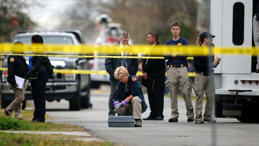 An evidence team works the scene where a sheriff's deputy was shot in the Lower 9th Ward of New Orleans Tuesday.