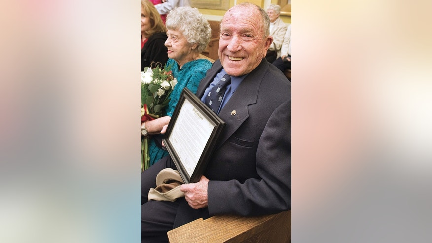 "In this 2012 photo, Elmer Melchi smiles as he sits with his wife, June, after commissioners proclaimed it ""Elmer Melchi Day."""