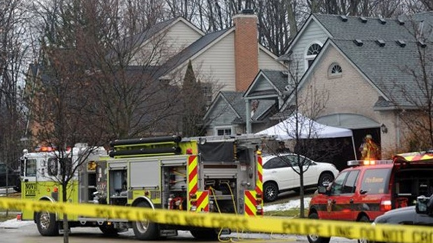 Police and fire officials investigate a house fire that killed five people at a home in Novi, Mich., Sunday, Jan. 31, 2016.
