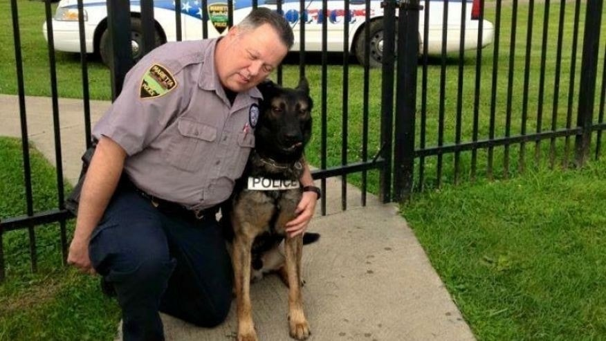 Matthew Hickey puts his arms around K-9 partner Ajax. (gofundme.com)