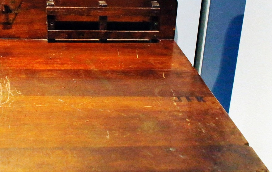 "In this Thursday, Nov. 5, 2015 photo, a detail shows the initials ""JFK,"" right, on a desk displayed in the exhibit titled ""Young Jack"" at the John F. Kennedy Presidential Library and Museum in Boston. An archivist at Choate, the private school in Connecticut where the president studied as a boy, insists the desk didn't belong to him. (AP Photo/Steven Senne)"