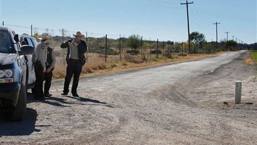 In this Saturday, Feb. 6, 2016 photo, Uvalde County Sheriffs Deputies guard the intersection to a neighborhood several miles outside of Uvalde, Texas.