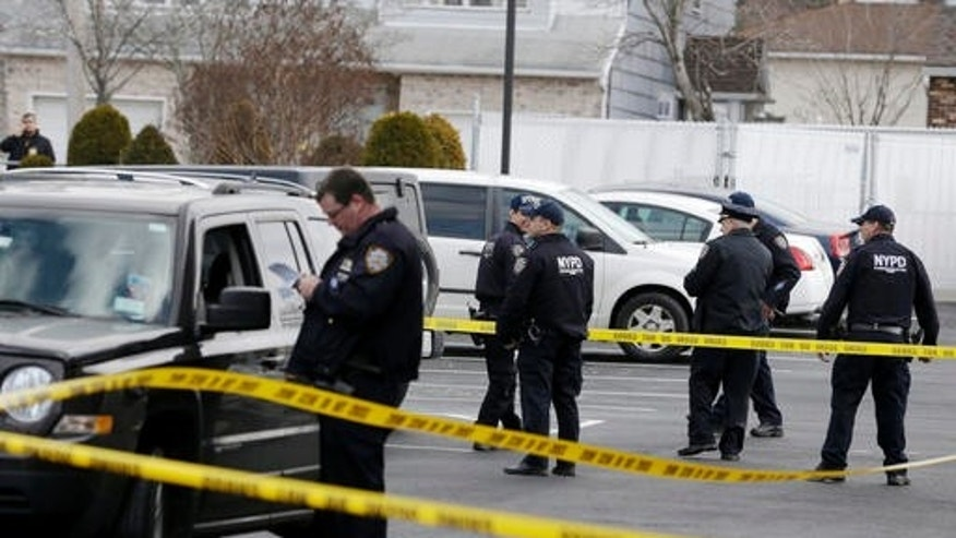Police officers stand in the parking lot of a Ramada Inn, where authorities say a man stabbed a woman and her children in the Staten Island borough of New York, Wednesday, Feb. 10, 2016. (AP Photo/Seth Wenig)