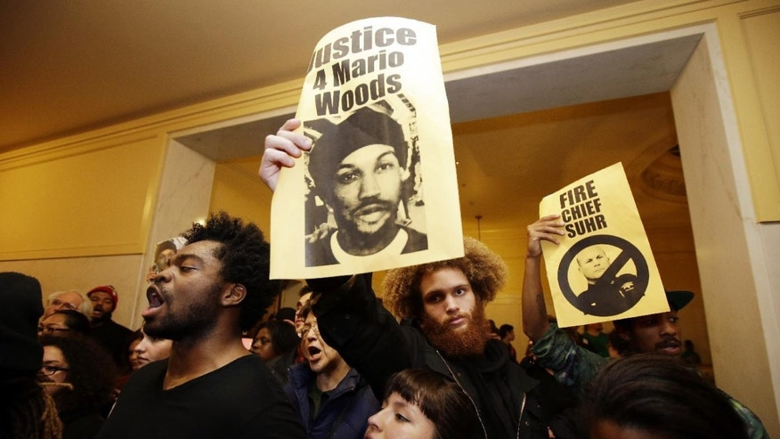 Demonstrators hold signs outside of a crowded San Francisco police commission hearing in December.
