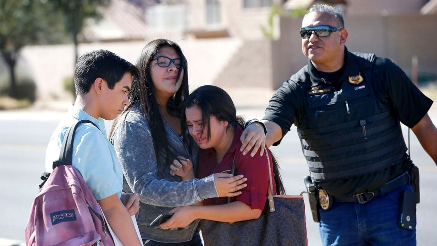 Students embrace after leaving campus, Friday, Feb. 12, 2016, in Glendale, Ariz.
