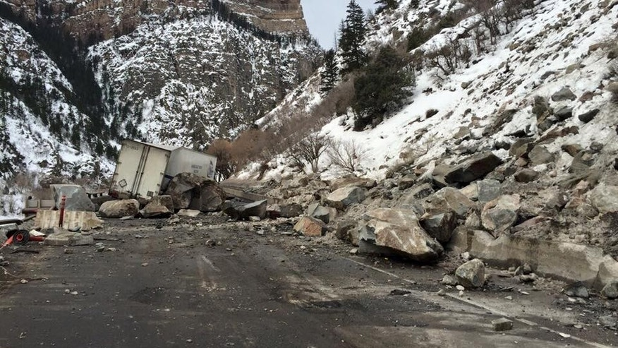 In this Tuesday, Feb. 16, 2016, photo provided by the Colorado Department of Transportation, state highway workers examine debris from a Monday rock slide on Interstate 70 in Glenwood Canyon in western Colorado.
