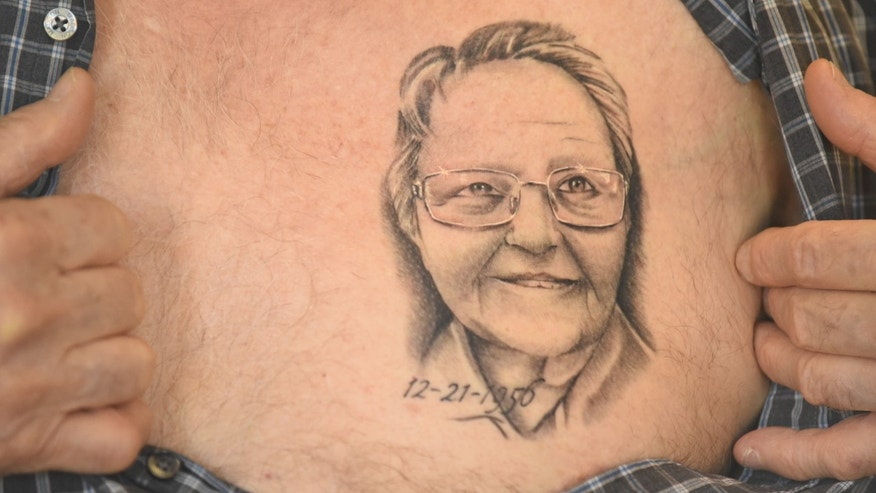 Arthur Burch shows a portrait of his wife's face tattooed on his chest.
