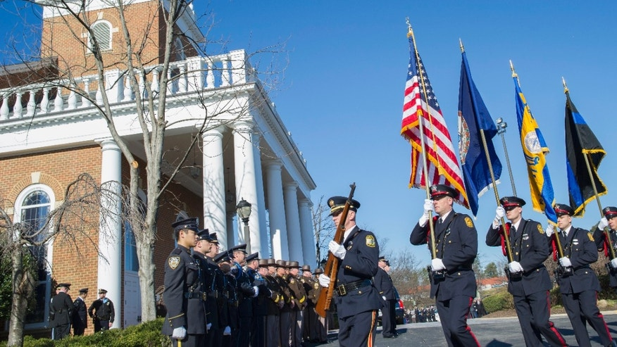 A police honor guard marches by the Hylton Memorial Chapel.