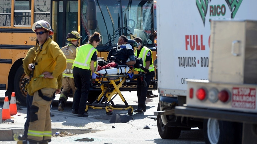 A man is transported to an ambulance at the scene of an accident involing a stolen taco truck and a school bus.