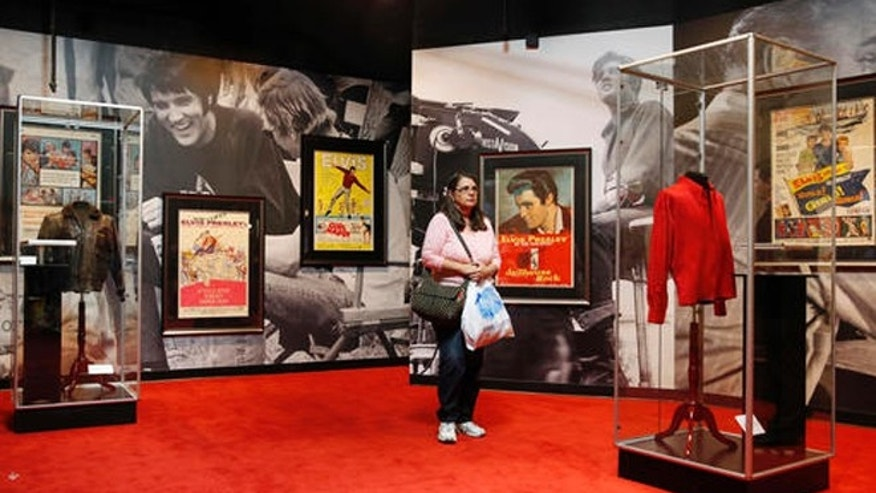 "In this April 23, 2015 file photo, a woman tours an Elvis exhibition on the first day of ""Graceland Presents Elvis: The Exhibition - The Show - The Experience"" at the Westgate Las Vegas hotel in Las Vegas."