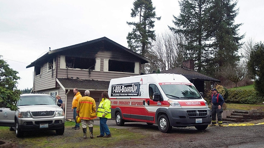Lewis County Coroner Warren McLeod and his staff work at the site of a house fire where three children perished Friday, March 4, 2016, in Centralia, Wash.